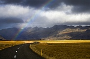 Rainbow over a rural road - Iceland